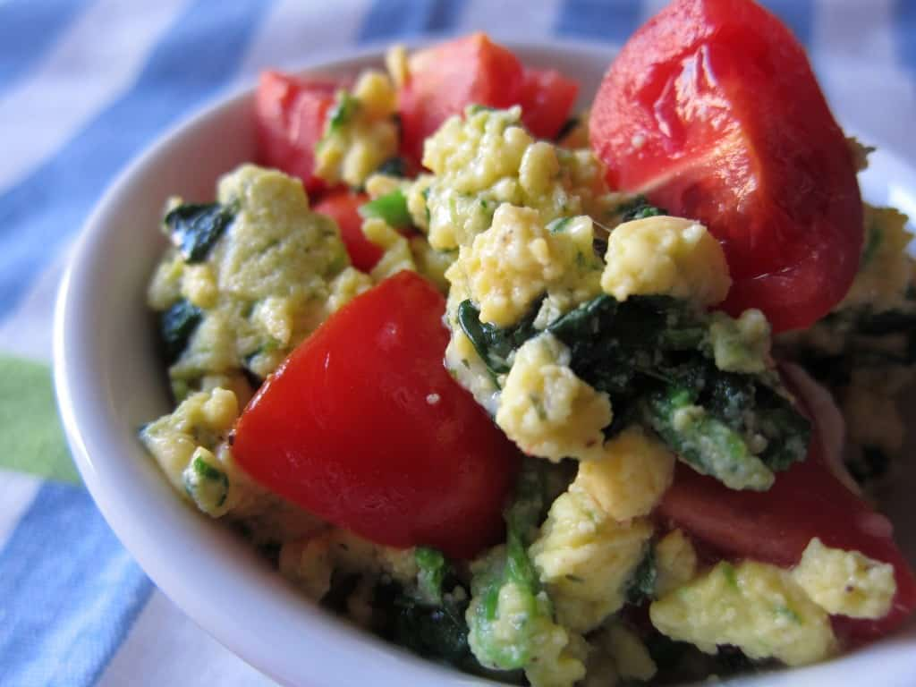 Eggs scrambled with spinach, cheese and tomato