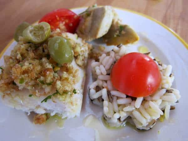 Roasted fish with breadcrumbs, rice, tomatoes, artichokes and olives