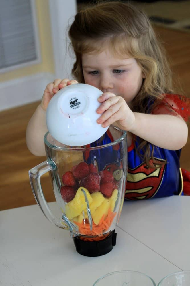 violet adding berries to rainbow smoothies